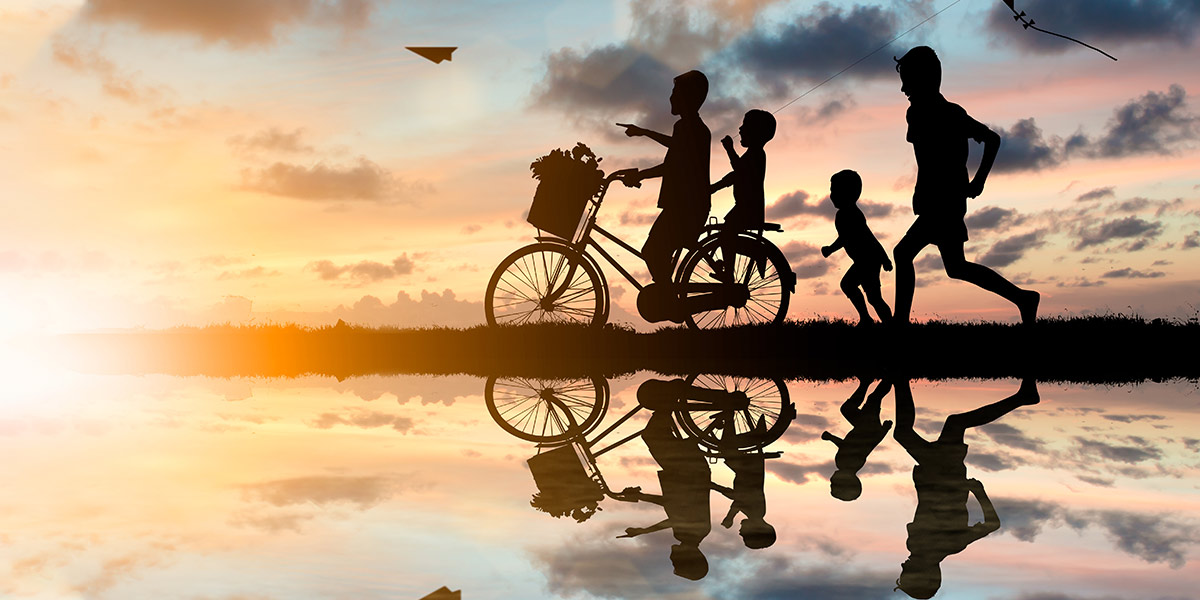 Silhouettes of kids ob bicycles with a sunset background