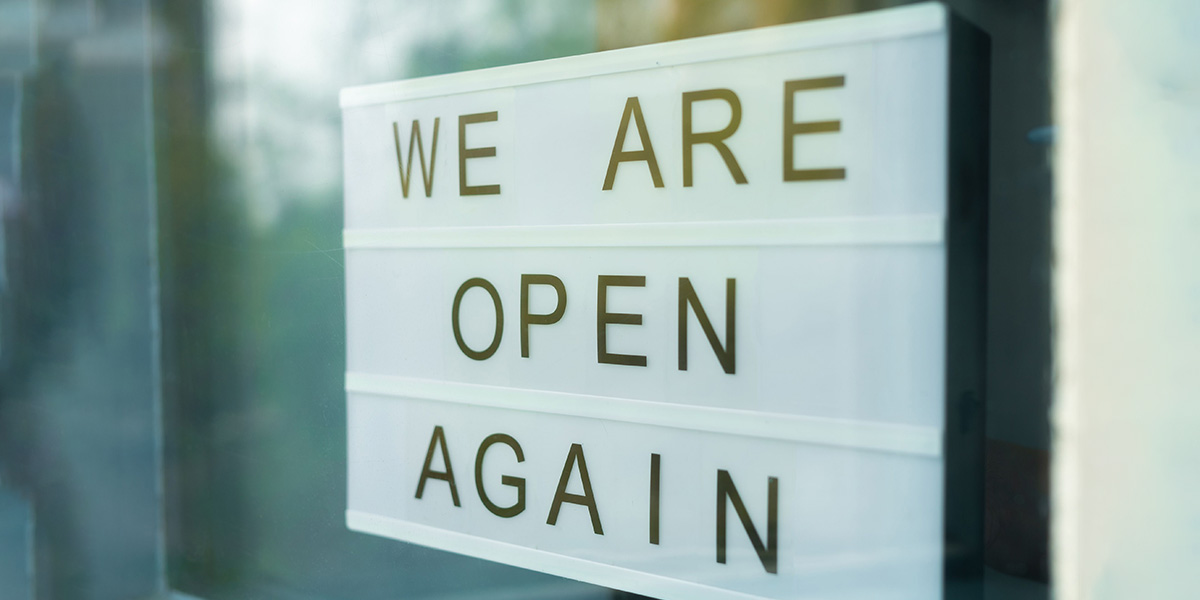 We are open again sign on a window