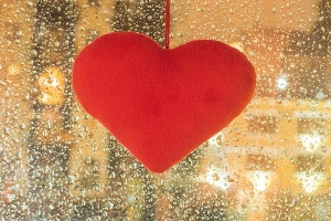 Red heart hanging on a rainy window