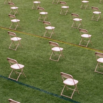 Socially distanced chairs arranged in a field